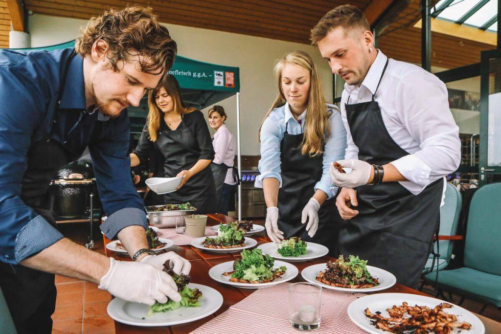 Grillakademie Anrichten der gegrillten Bacon Spieße mit echt hällischer Bauernbratwurst auf sommerlichem Salatbeet