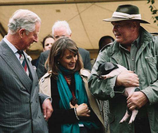 Rudolf Bühler im Gespräch mit Prinz Charles mit Schwaebisch Haellischem Ferkel auf dem Arm hat