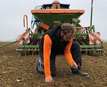 Landwirt Markus Ehrmann auf dem Acker, hinter ihm Traktor und Sämaschine.