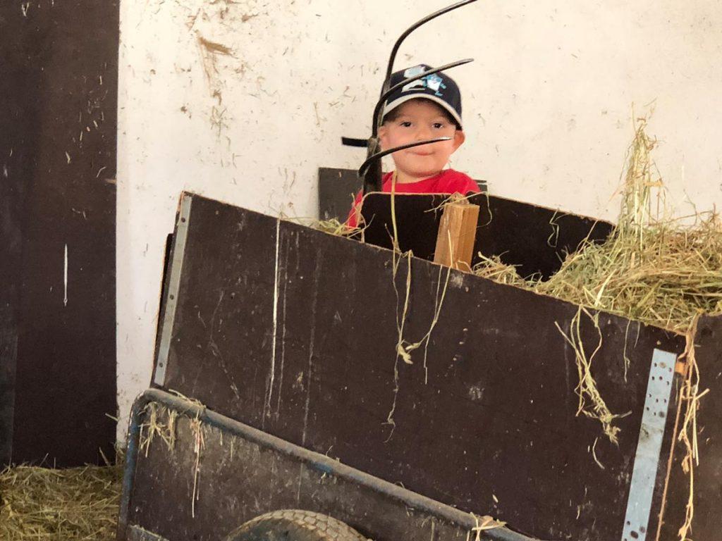 Junior Rafael mit der Heugabel im Pferdestall.