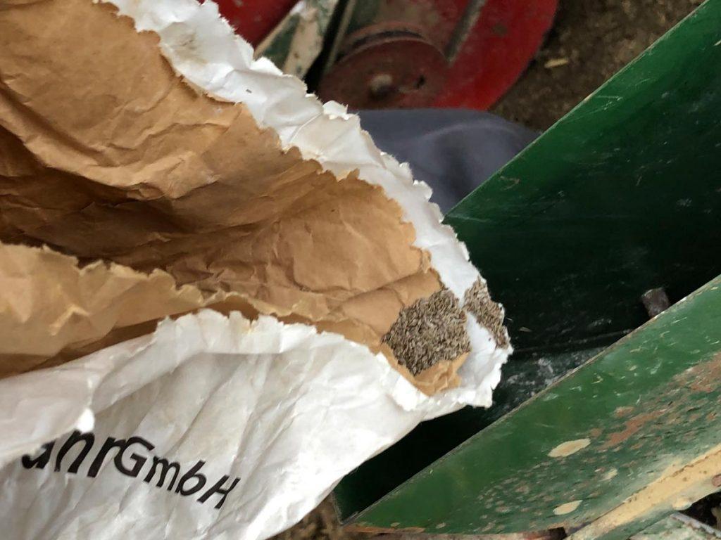 Der Landwirt füllt das Saatgut in die Behältnisse der Maschine.