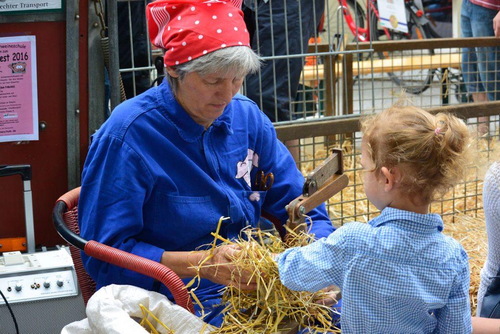 Kerstin Gronbach, Bäuerin aus Hohenlohe, bindet mit den Kindern Strohballen