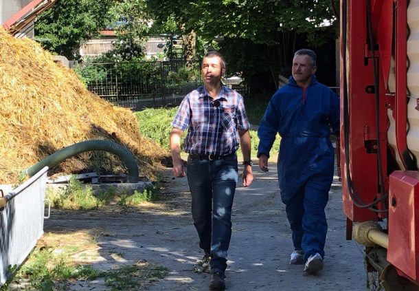 Kontrolleur Klaus Strohm im blauen Schutzanzug beim Rundgang mit Hofbesitzer Albrecht Löblein.