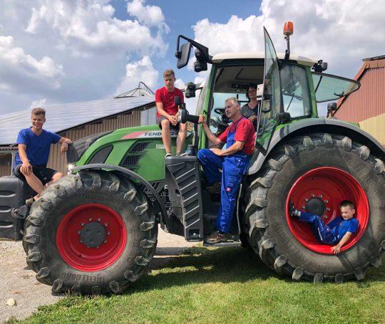 Familienfoto auf dem Traktor: Sibylle und Gerhard Kümmerer mit ihren Söhnen Luka, Fabio und Mika.