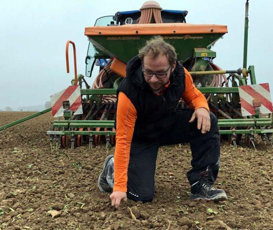 Markus Ehrmann kontrolliert die Beschaffenheit des Bodens auf einem Acker.